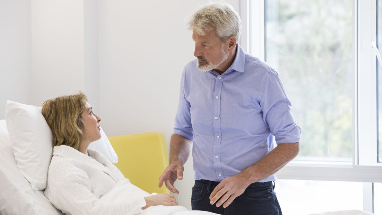 A consultant speaks to a patient in bed
