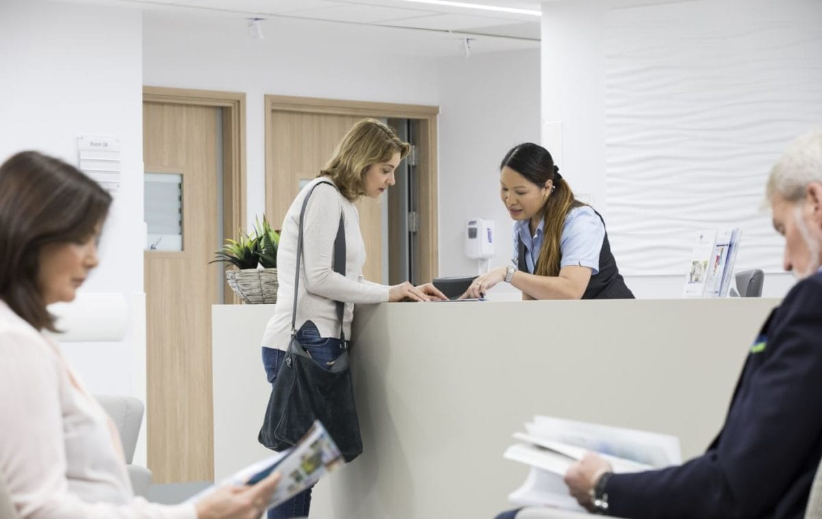 A receptionist explains a form to a patient