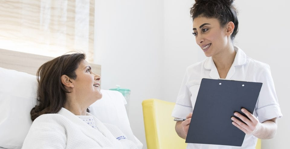 Nurse talks to a patient in bed